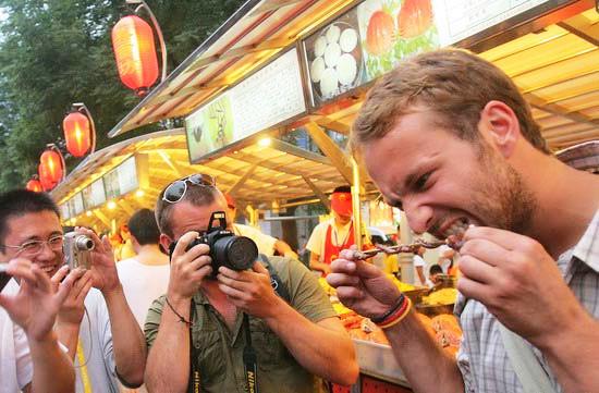 外国游客在北京东华门夜市品尝中国传统小吃